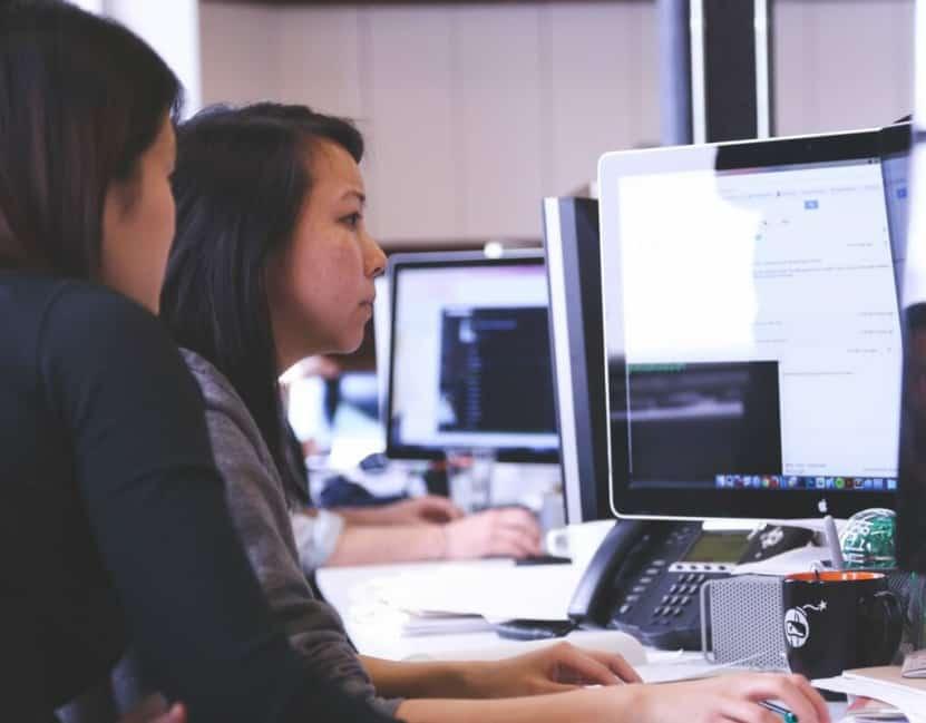 Diverse women looking at computer monitor